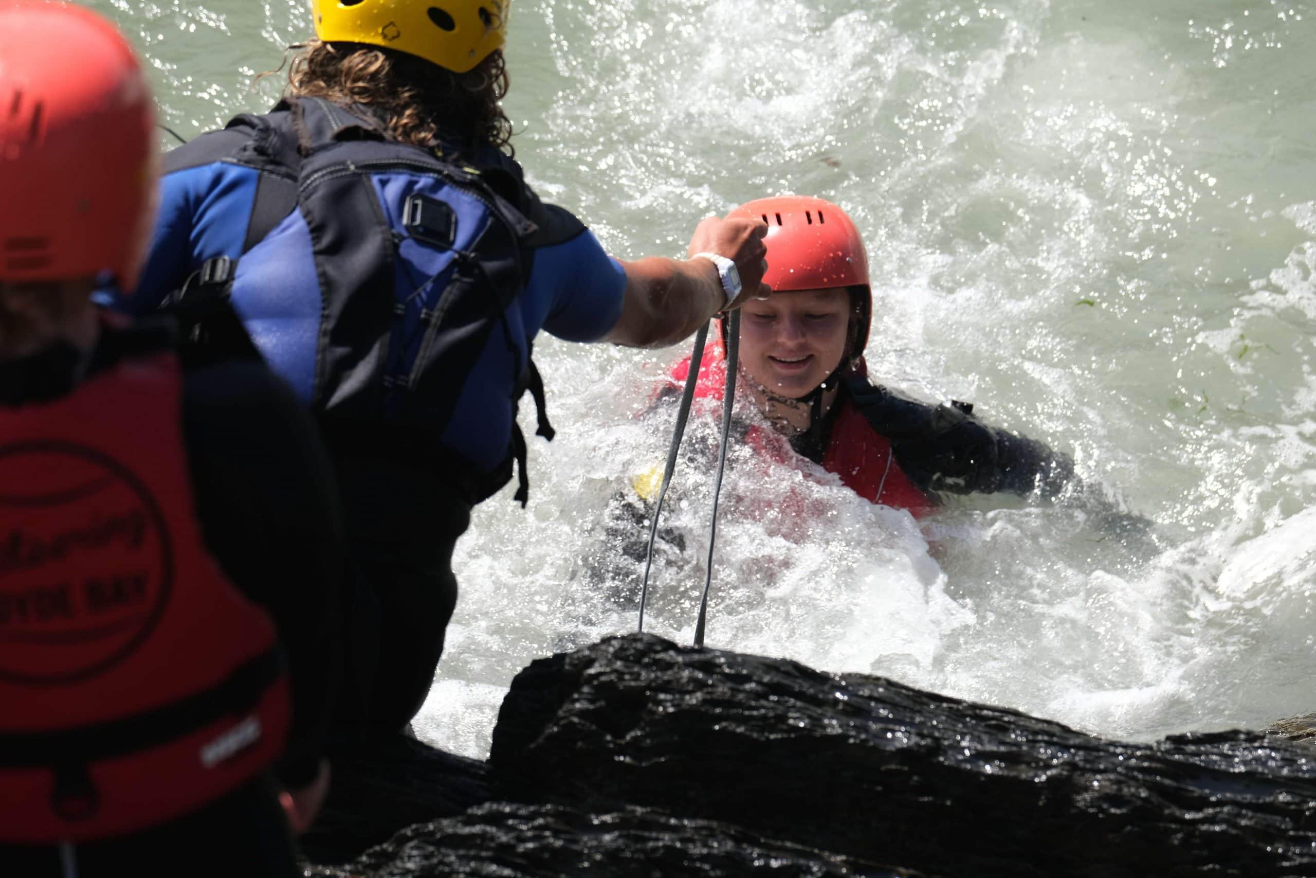 climbing up rocks while coasteering in north devon